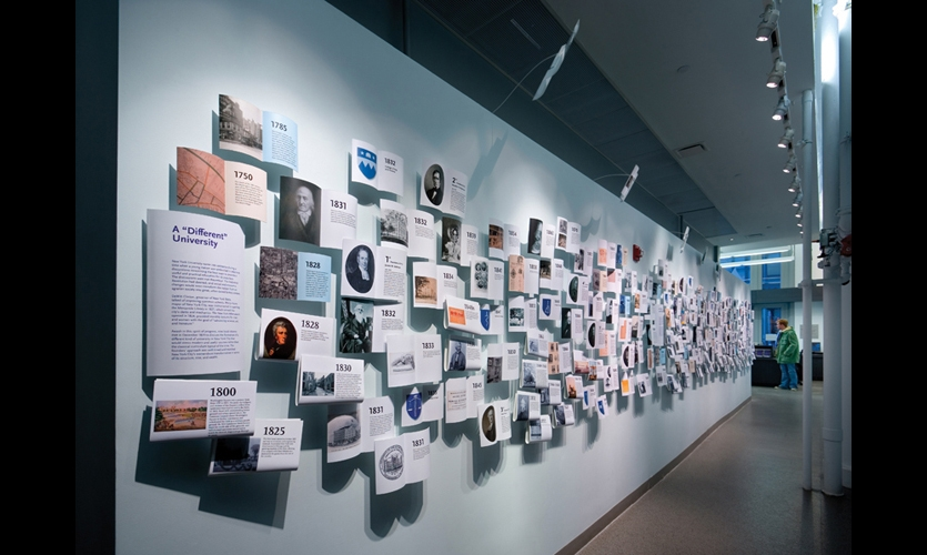 For the timeline at New York University's welcome center, C&G Partners employed the metaphor of a book exploding on a wall, and later repurposed the exhibit graphics as an actual book. (Fabrication: Exhibitology. Photo: ESTO/David Sundberg)