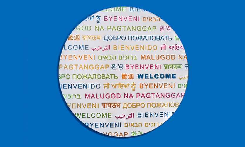 """Detail on the welcome wall repeats """"welcome"""" in 14 languages and uses all the colors seen throughout the space."""