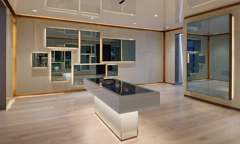 The space is brightly lit, glossy and bedecked with framed mirrored surfaces, which can be activated by the touch of one of four golden objects on the central table.