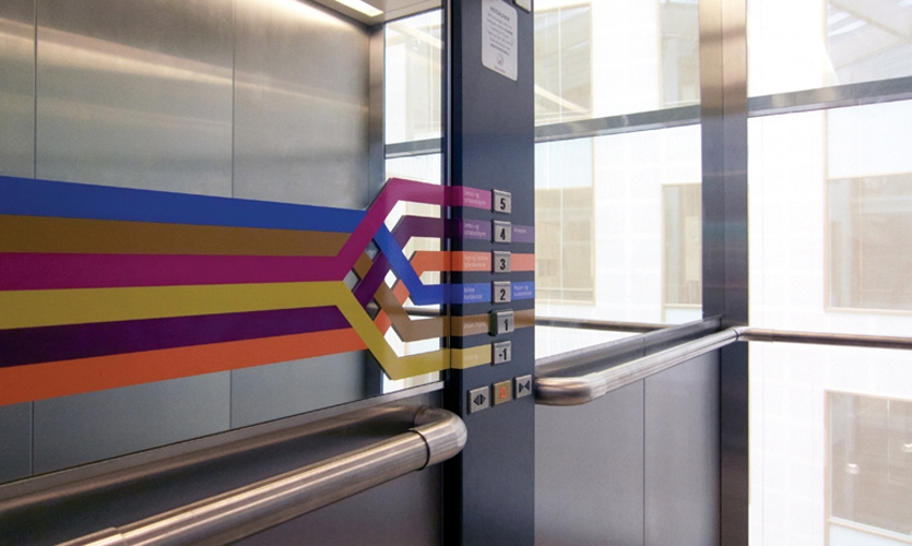 Inside elevators, the color bands are flipped on their sides and integrated with floor buttons.