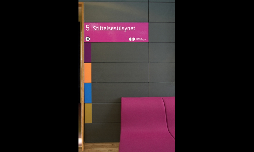 Four entrances to each floor are signed with corresponding color bands on stone walls. The bright colors add visual punch to a subdued materials palette.