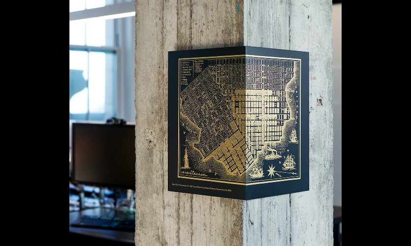 These vignettes are silkscreened in metallic gold on aluminum panels painted to look like the blackened steel found elsewhere in the space.