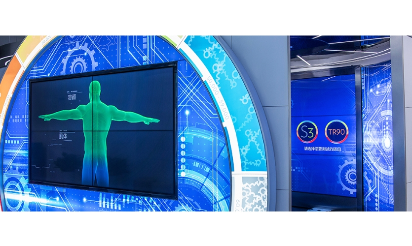 The body scanning experience is flanked by interactive screens (image: body scanning niche with tech graphics)