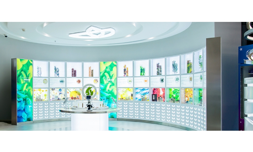 In the Pharmanex zone, the SLD team has expertly created a light, bright and inviting space using wall fixtures stacked with light box fixtures, raw botanical ingredients and digital interactives. (image: gallery-like retail space)
