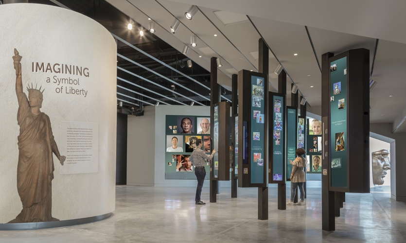 """Visitors enter the Engagement gallery and follow Liberty's story along curved walls that evoke the copper folds of the Statue; from there, we can also see """"Becoming Liberty"""" where visitors can take self portraits. (Photo: David Sundberg / Esto)"""