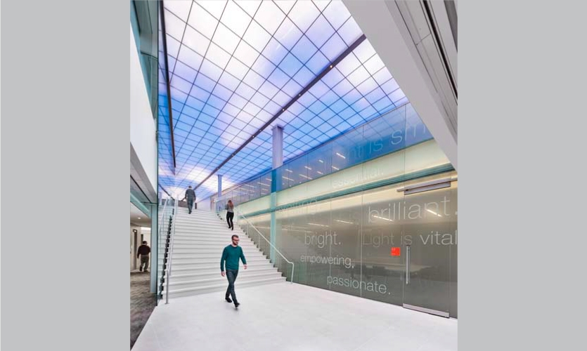 """The main lobby features a double-height staircase featuring inspirational """"light is"""" statements in various transparencies. (Photo: Anton Grassl/Esto)"""