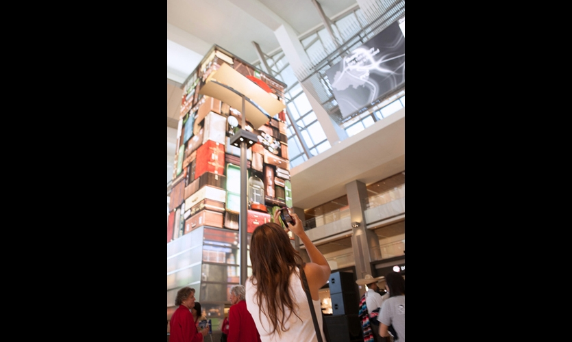 The Time Tower is a four-sided mediascape wrapped around an elevator core. Here, it displays the classic kitschy luggage tower found at many airports. The tower's base of diffused glass is an interactive surface that responds to the gestures of passersby, triggering real-time visual effects. (Photo: Moment Factory)