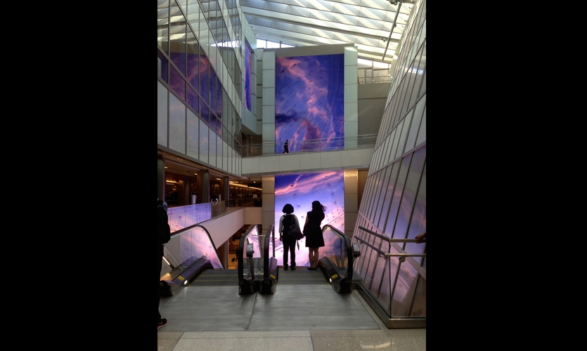 """As arriving passengers descend an escalator toward baggage claim, they're greeted with a stunning mediascape: an 80-foot-tall """"Welcome Wall"""" that displays high-definition imagery is accompanied by welcome greetings in languages keyed to the arriving flights. (Photo: Sardi Design)"""