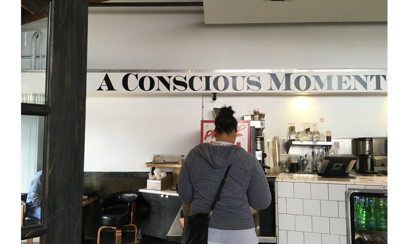 """Self Conscious Messaging: This cafe wall sign continues """"...of indulgence."""" This simplistic style of """"deep"""" consciousness messaging ruins the moment for me. Being literal about subtle experience cheapens it."""