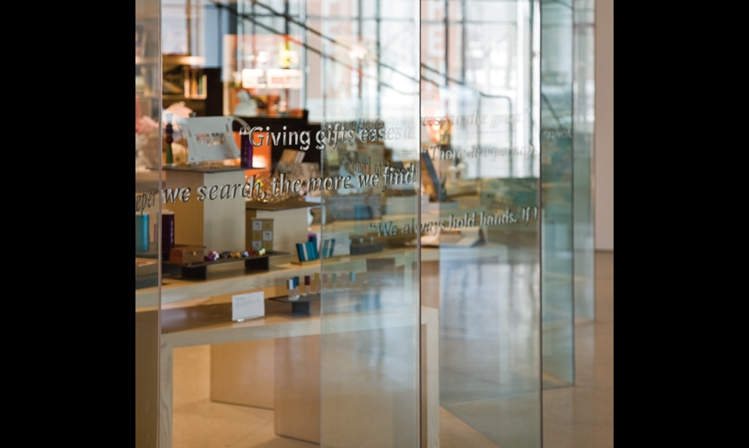 The gift shop's zig-zagging glass wall echoes the facade. Quotes and sayings about gift-giving are applied in vinyl text to the glass.