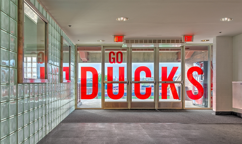 "Doors that lead to the athletic field are adorned with translucent red letters that display the school's cheer ""Go Ducks."""