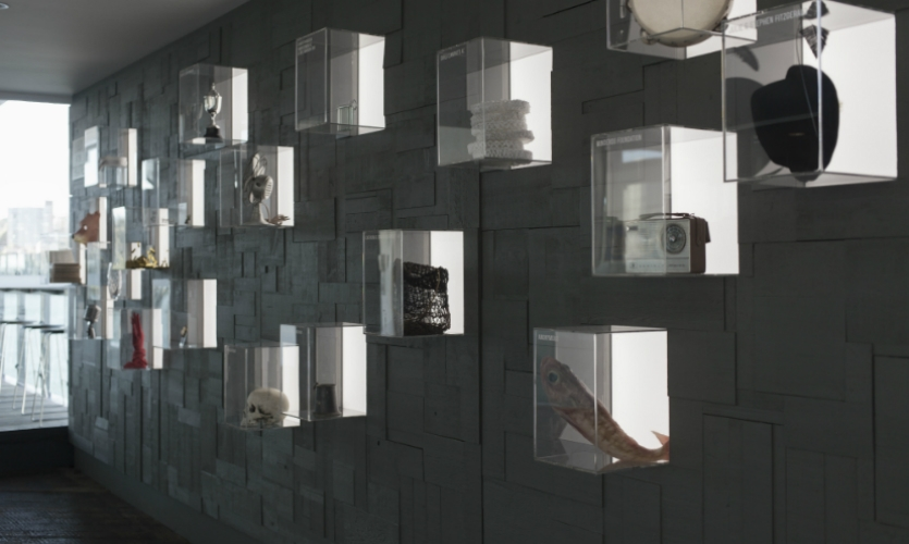 Collider designed a wall of clear, backlit boxes that contain iconic props and wardrobe pieces from the company's productions.