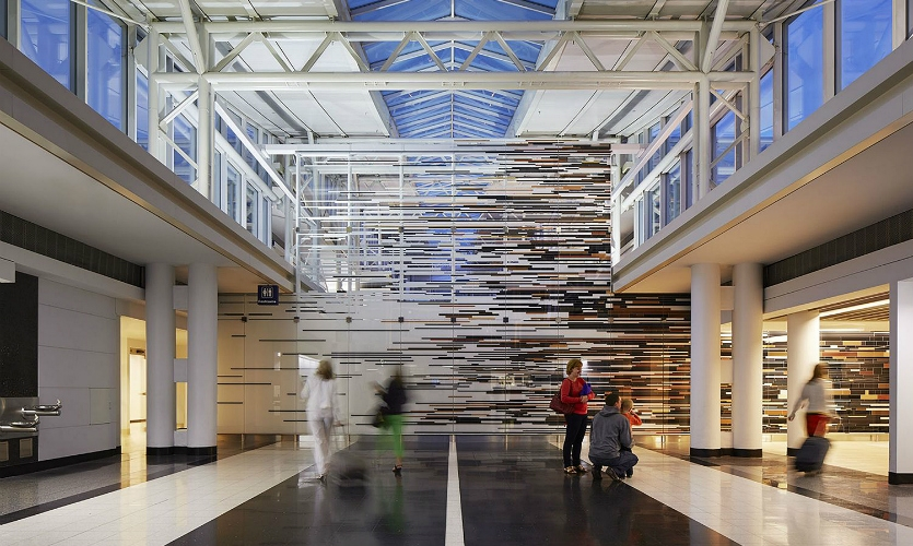 The two-story mural is translucent at the top to let light stream into the terminal, and opaque at the bottom to hide functional areas behind the wall.
