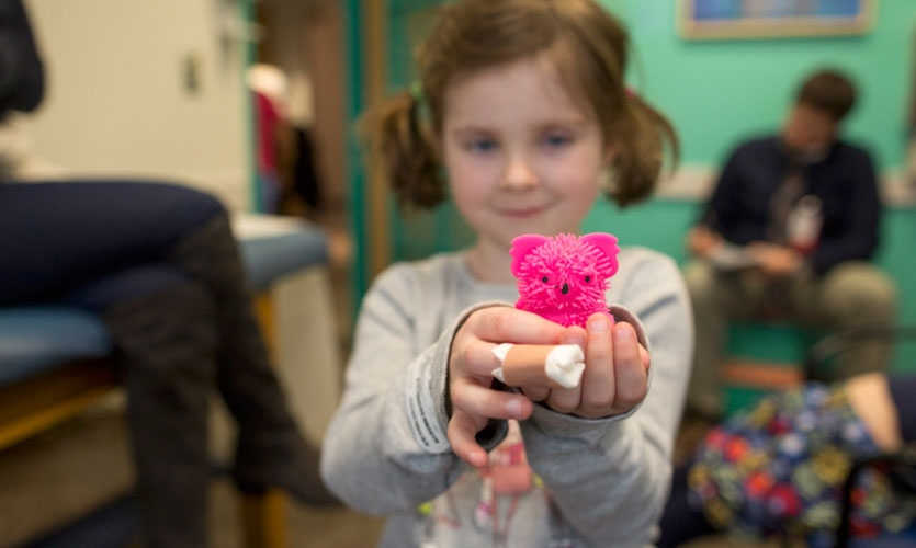 Our brave little patient with a freshly poked finger shares her prize from the toy box.