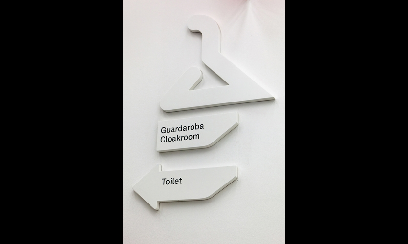 Enameled-MDF amenity signs are inspired by the clipped forms of the building itself.