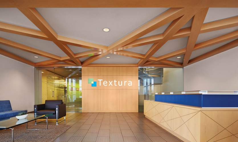 Just inside the lobby, architectural ceiling features draw the eye toward the Textura brand mark.