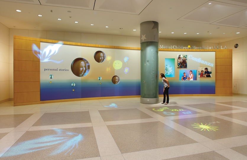 The 48- by 12-ft. dynamic welcome wall includes projected motion video, rear projection displays (circles), digital supergraphic wallpaper, lenticular panels, 50-in. plasma screens, and dimensional letters.