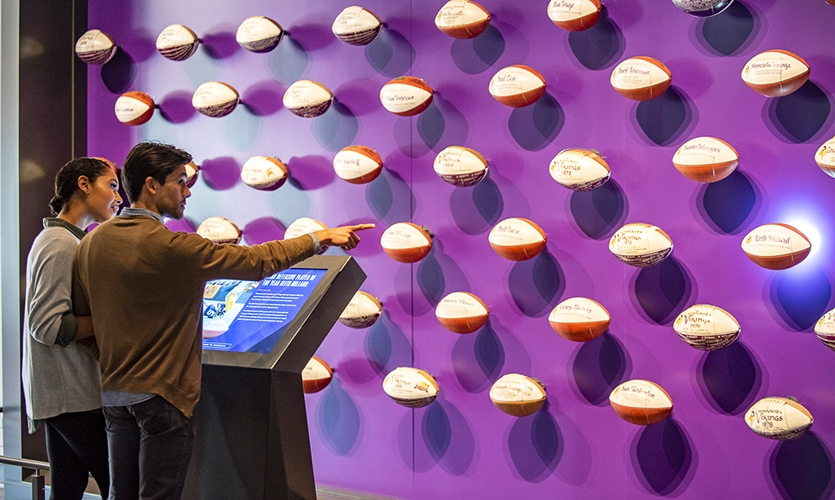 """The """"Historic Game Ball Wall"""" a collection of footballs from notable games mounted with lights behind each, is turned on by a selection on the touch panel in front of the display."""