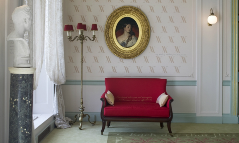 Visitors are immersed in the words and symbols of Queen Victoria, whether printed on the carpet or wallpaper or silkscreened onto furniture upholstery.