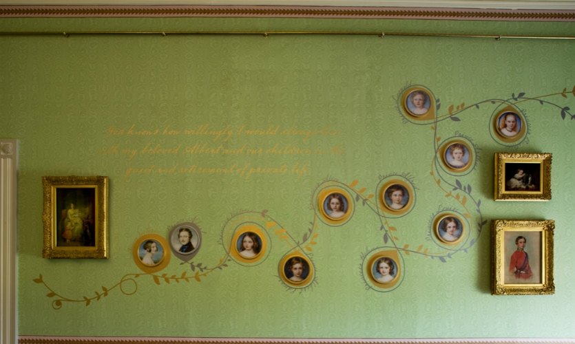Hand-painted gold and silver scrolling vines wrap around the portraits of Victoria's nine children, delicately spelling out their names.