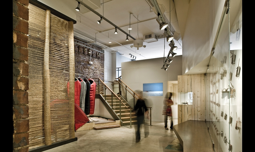 "In the store's community area, Patrick Marold's woven wall/sculpture reflects the artist's ""economy of material"" philosophy of minimizing waste and re-using materials as much as possible. Its structure makes it an ideal collection point for visitors' stories and images. The use of beetle-kill pine logs here and elsewhere in the store highlights a regional environmental dilemma."