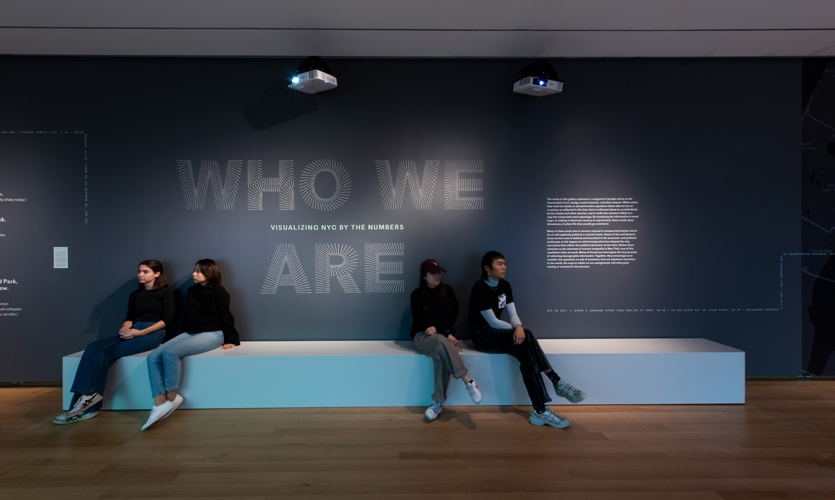 In the Main Gallery, the exhibition title is screenprinted behind a long bench, inviting visitors to enjoy the projected visualizations.