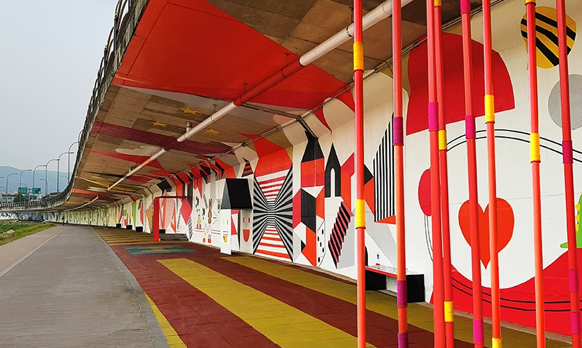 The Yulha Play Zone covers a 250 meter length of riverside walk with mixed media graphic installations in an unexpected setting. (image: brightly-painted underpass with seating)