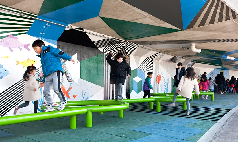 Graphics not only exist from floor to ceiling, but playground equipment was also custom fabricated as a pop-out form of graphic as well. (image: children playing on winding green plaything)