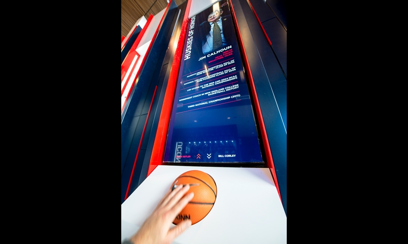 The three interactive kiosks in each wing use an actual UConn basketball filled with foam as a giant trackball to navigate a custom CMS.