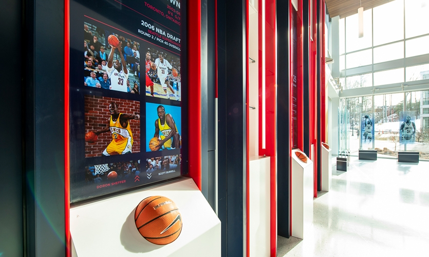 Throughout the graphics, built-ins and brand imagery, the DI design team has mimicked the verticality of the space and the game using noticeable vertical striping.
