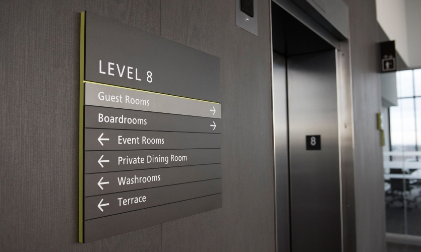 The interior wayfinding references the visual language of the Centennial College brand through the use of alternating gray tones and accented green edges that are present on all college-use signage