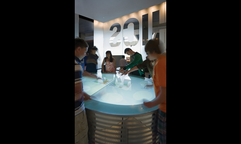 The 7-by-5-ft. glass-and-stainless steel Ethics Table pits visitors against each other as they race to assemble a front page while trying to answer ethical questions correctly.