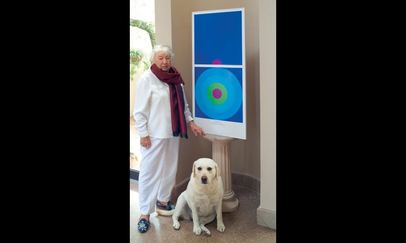 Jane Davis Doggett with her dog Liberty and her artwork, which borrows the simple shapes and bold colors of signage. At 84, she is still working, drawing from her background with Josef Albers to develop two- and three-dimensional graphic works, some of which are in the permanent collection at Yale.