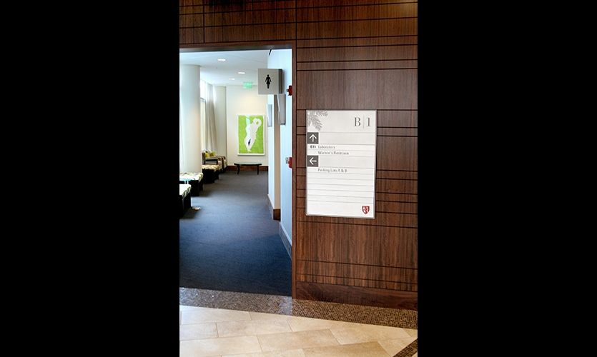 KKA's signage system for Stanford uses rich materials including dark wood, glass, and etched metals.