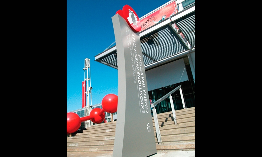 12-ft.-high curved aluminum pylons are topped with 3-ft.-diameter red disks bearing pictograms for major attractions and amenities. Minimal text is provided in English, French, and Spanish.