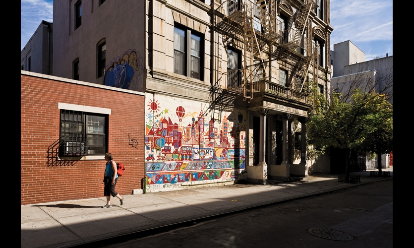 Graffiti often has an underlying social message. The bright, geometric cityscape covering this tenement wall speaks to the bland urban condition surrounding it.