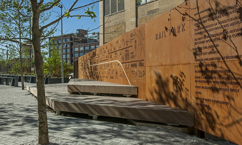 """The laser-cut wall serves as a quiet backdrop for the park and the stage that sits in front of it as well as providing an iconic """"meeting point"""" for families, groups and tours."""