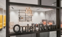 Amenity Spaces like the Ray Kroc room in Hamburger University and Quiet Rooms are identified with large dimensional letters in a blackened steel finish that integrate with the architecture