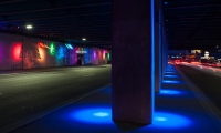 The center columns are washed with a luminous blue light. The suspended features are programmed to move in the direction of traffic, sweeping the length of the underpass.