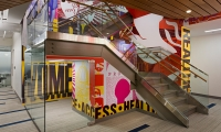 The main mural ascends through a three-story staircase at the center of the office.