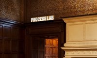 "A glowing sign floats above the door of the ""Process Lab,"" a dynamic new interactive space."