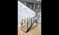 Iconic front pages from The Post archives fill a large feature wall at the interconnecting staircase, subtly executed in a contrasting glossy/matte print.