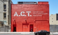 Stenciled graphics are illustrated on the exterior wall at the rear of the theater.