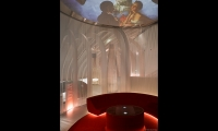 "Visitors lie in repose at ""Bacchus and Venus,"" gazing up at images of wine and love swirling across the domed ceiling."