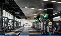 An iconic action shot of Troy Aikman, UCLA's most recognizable former player, is represented on a double-height wood panel overlooking the weight room.