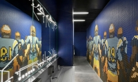 A restroom features a tile mosaic recreation of a UCLA football image, while football plays have been sandblasted along top and bottom of the mirror.