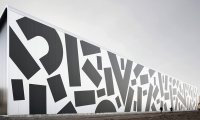 They created a typographical camouflage pattern that covers an enormous façade.