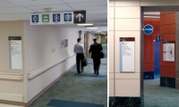 This photo shows many components of the pathway and Access wayfinding system at M.D. Anderson Cancer Center, to include a wall directional, overhead directional, blade signs and icons.