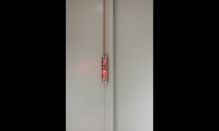 Suspending the meeting room signage in front of the wall surface allows the design to be equally effective on solid or transparent walls. (image: vertically suspended red LED sign)