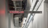 """Illuminated destination identification draws attention to the numerous unique labs and workshops within the open plan workspace. (image: lit """"soundlab"""" sign)"""